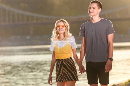 young couple walking on river beach in evening and holding hands