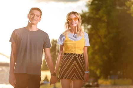 Photo for Smiling young couple holding hands on river beach in evening and looking at camera - Royalty Free Image