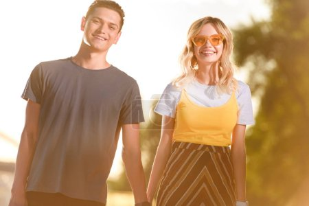 smiling young couple holding hands on river beach during sunset and looking at camera