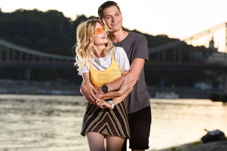 smiling boyfriend hugging girlfriend on river beach in evening