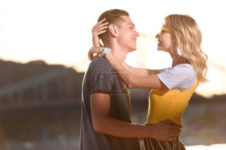 Photo pour Vue latérale du couple souriant s'embrassant et se regardant sur la plage de la rivière en soirée - image libre de droit