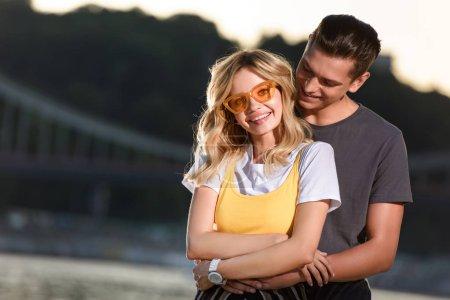 boyfriend hugging smiling girlfriend on river beach in evening