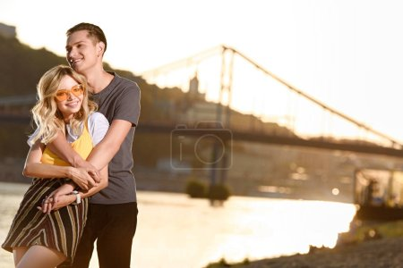 boyfriend hugging girlfriend on river beach during sunset