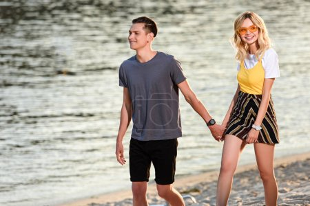 young couple holding hands and walking on river beach in evening