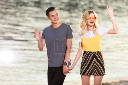 young couple walking on river beach in evening and waving hands to someone