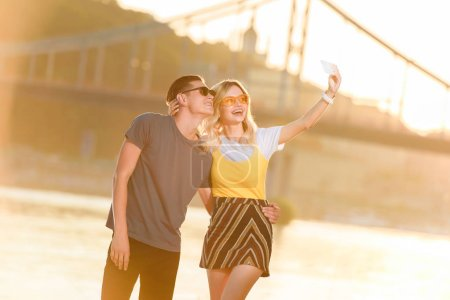 happy young couple taking selfie with smartphone on river beach in evening