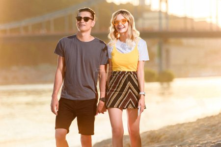 young couple in sunglasses holding hands on river beach in evening