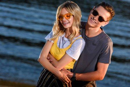 cheerful boyfriend cuddling girlfriend on river beach in evening
