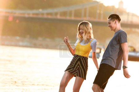 young couple having fun and looking down on river beach in evening