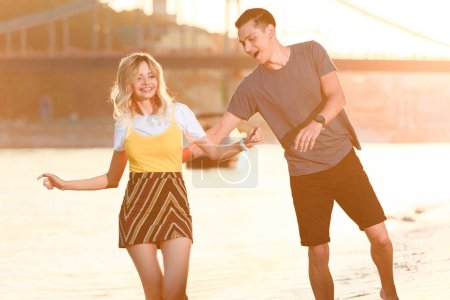 laughing young couple having fun on river beach during sunset