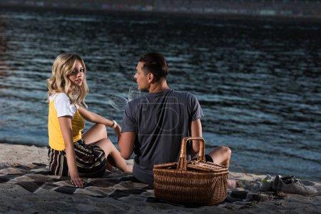 Photo pour Jeune couple assis sur une couverture avec des verres à vin sur la plage de la rivière le soir - image libre de droit
