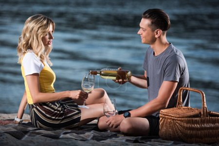 side view of boyfriend pouring wine in glasses at picnic on river beach in evening
