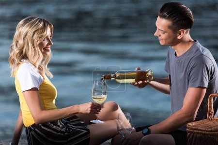 cheerful boyfriend pouring wine in glasses at picnic on river beach in evening