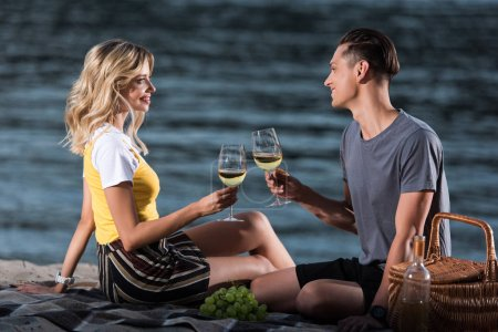 side view of smiling couple clinking with wineglasses at picnic on river beach in evening