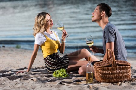 young couple having fun at picnic on river beach in evening