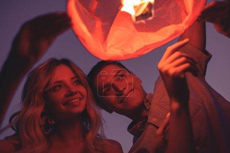 friends launching sky lantern on river beach in evening