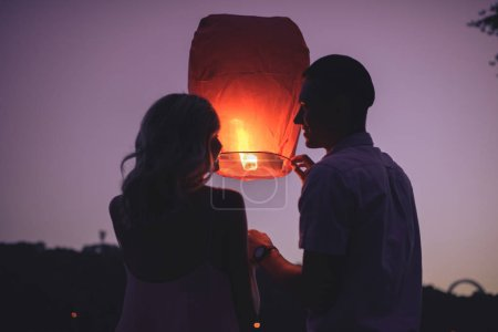 silhouettes of couple launching sky lantern on river beach in evening and looking at each other