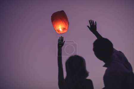 silhouettes of couple waving hands to flying chinese lantern in violet evening sky