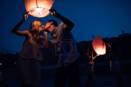 young couple kissing and holding sky lantern on river beach in evening