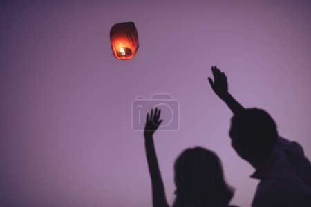 silhouettes of couple waving hands to flying sky lantern in evening