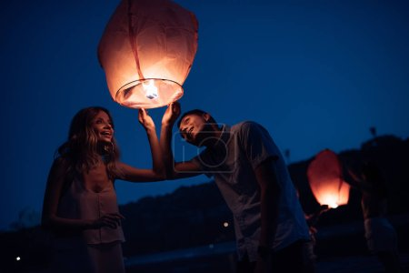 young couple looking at sky lantern on river beach in evening