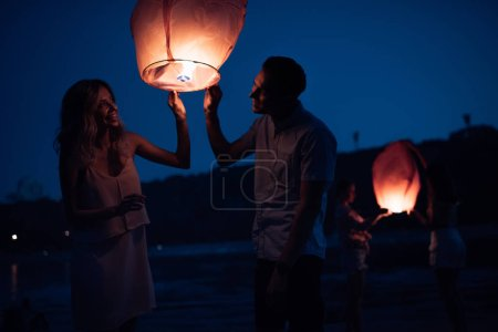 Photo for Happy young couple launching sky lantern on river beach in evening - Royalty Free Image