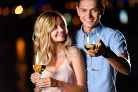 selective focus of young couple holding glasses of wine on river beach in evening