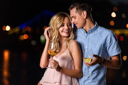 happy young couple standing with glasses of white wine on river beach in evening