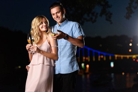 smiling young couple standing with glasses of wine on river beach in evening