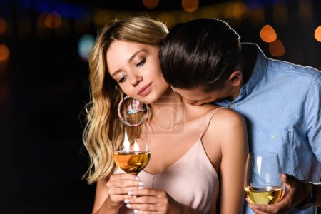 boyfriend kissing girlfriends shoulder and they holding glasses of wine in evening