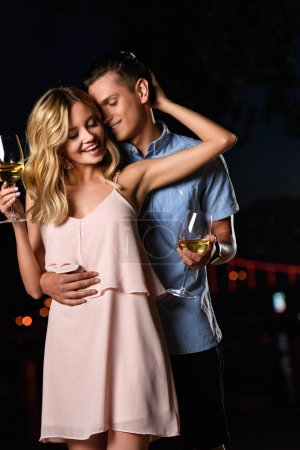 young couple hugging and holding glasses of wine on river beach in evening