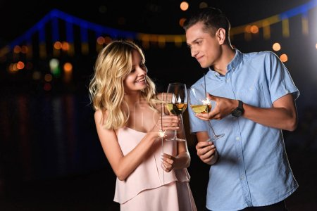 young couple clinking with glasses of wine on river beach in evening