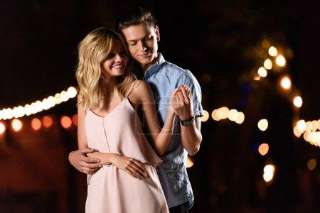 boyfriend hugging girlfriend on river beach in evening