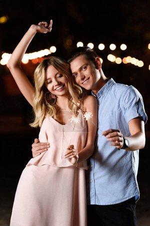 Photo pour Heureux jeune couple dansant et faisant la fête scintille sur la plage de la rivière en soirée - image libre de droit