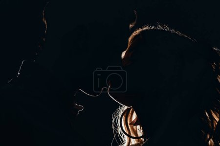 Photo for Side view of silhouettes of heterosexual couple kissing in dark - Royalty Free Image