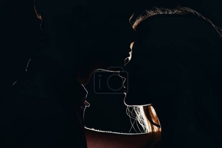 silhouettes of young tender couple in dark