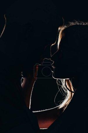 Photo pour Silhouettes de jeune couple tendre va embrasser dans l'obscurité - image libre de droit