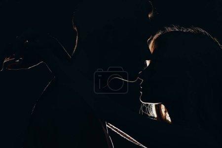 silhouettes of boyfriend kissing girlfriends nose in dark