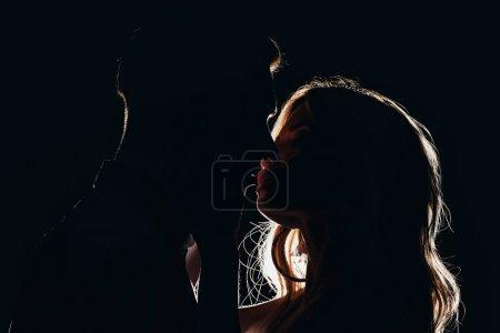 Photo pour Silhouettes de couple hétérosexuel sensuel embrasser dans l'obscurité - image libre de droit