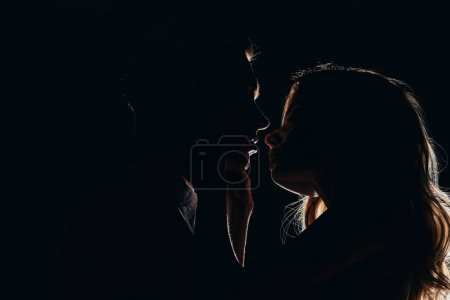 Photo for Silhouettes of boyfriend and girlfriend going to kiss in dark - Royalty Free Image