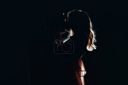 Photo for Silhouettes of passionate couple kissing in dark - Royalty Free Image