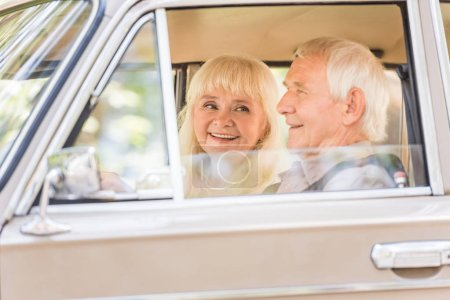 Photo for Side view of senior couple in beige vintage car - Royalty Free Image
