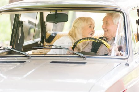 Photo for Senior man and woman smiling and driving vintage car - Royalty Free Image