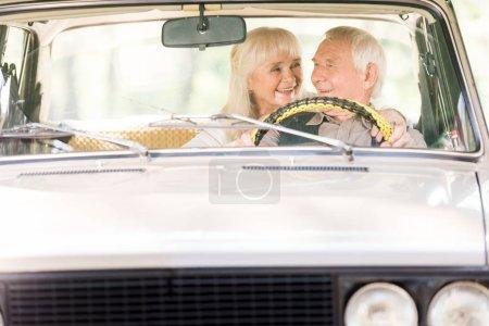 beautiful senior woman hugging man in vintage car