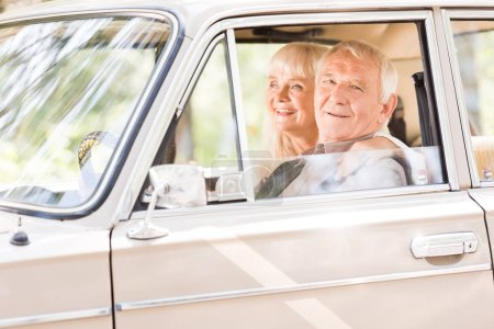 Photo for Senior woman embracing smiling man in beige car - Royalty Free Image