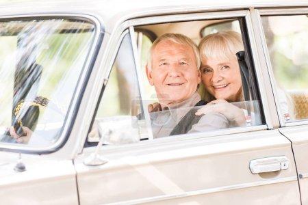 attractive senior woman hugging man in vintage car