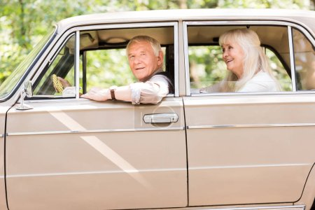 side view of smiling senior couple sitting in beige vintage car