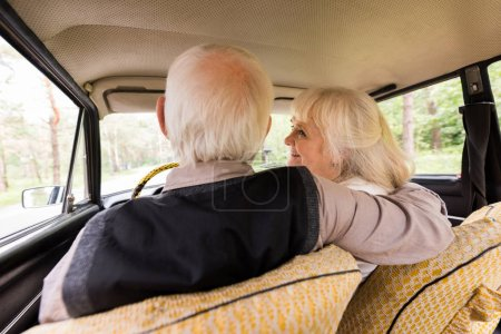 Photo for Back view of senior husband and wife in beige car - Royalty Free Image