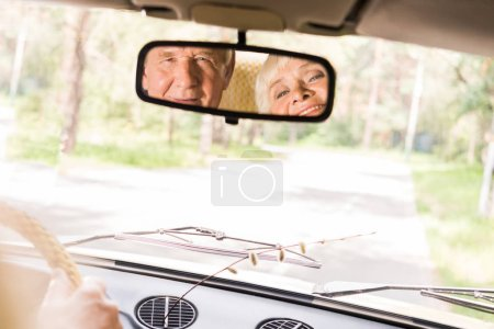 view of happy senior couple in rear window of vintage car