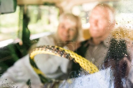 view through windshield of senior man and woman sitting in vintage car